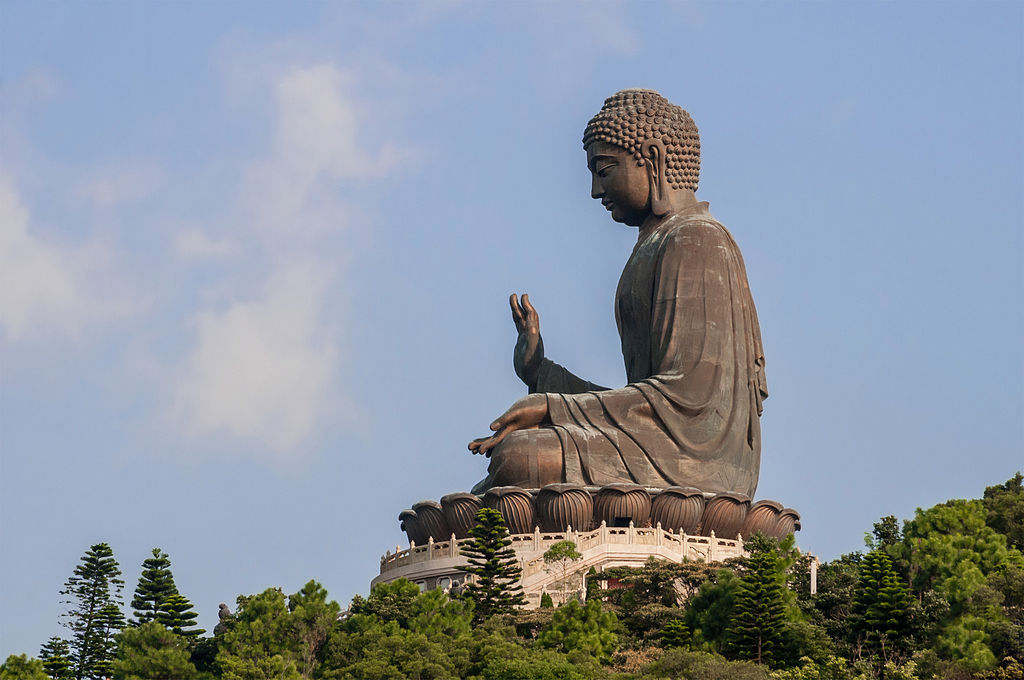 A huge, stone Buddha towers, meditating in profile, above the trees, with an open sky behind - Photo by Béria Lima De Rodríguez